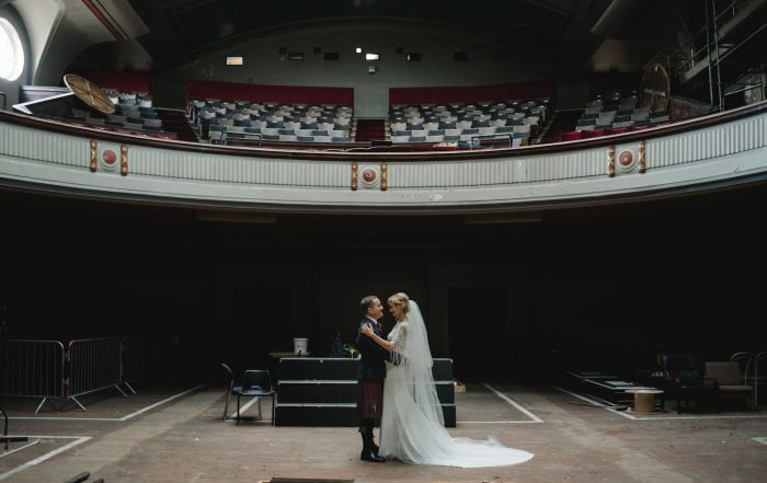 A married couple stand in an empty auditorium